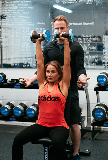 Personal Trainer in gym with female client